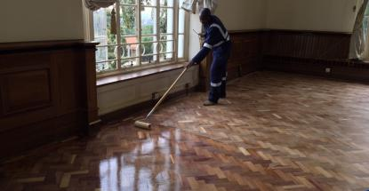 Hard at work restoring the wooden floor at Bulange, Mengo